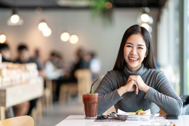 Porträt der jungen attraktiven asiatischen frau, die kamera betrachtet