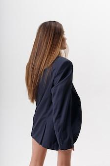 Porträt der jungen attraktiven asiatischen frau mit dem langen braunen haar, das blauen anzug trägt, lokalisiert auf weißer wand. dünne hübsche frau, die auf cyclorama aufwirft. modellversuche der schönen dame