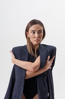 Porträt der jungen attraktiven asiatischen frau mit den langen haaren im schwarzen bodysuit und im blauen anzug lokalisiert auf weißem studiohintergrund. dünne hübsche frau, die auf cyclorama aufwirft. modellversuche der schönen dame
