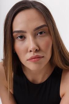 Porträt der jungen attraktiven asiatischen frau mit langen braunen haaren in der schwarzen kleidung, lokalisiert auf weißer wand. dünne hübsche frau, die auf cyclorama aufwirft. modellversuche der schönen dame
