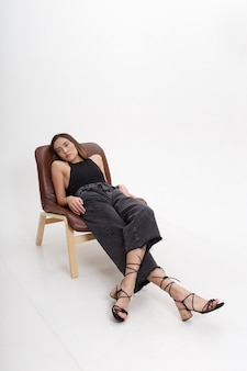 Porträt der jungen attraktiven asiatischen frau mit langen braunen haaren in der schwarzen kleidung, lokalisiert auf weißer wand. dünne hübsche frau, die auf stuhl auf cyclorama liegt. modellversuche der schönen dame