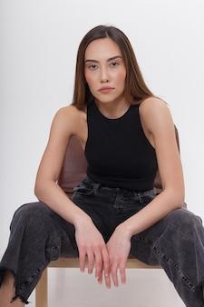 Porträt der jungen attraktiven asiatischen frau mit langen braunen haaren in der schwarzen kleidung, lokalisiert auf weißer wand. dünne hübsche frau, die auf stuhl auf cyclorama sitzt. modellversuche der schönen dame