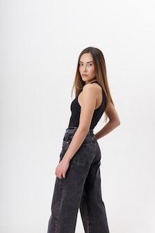 Porträt der jungen attraktiven asiatischen frau mit langen haaren im schwarzen body, jeans, lokalisiert auf weißer wand. dünne hübsche frau, die auf cyclorama aufwirft. modellversuche der schönen dame