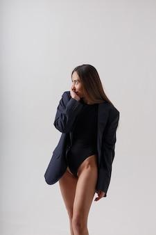 Porträt der jungen attraktiven asiatischen frau mit langen haaren im schwarzen body und im blauen anzug lokalisiert auf weißer wand. dünne hübsche frau, die auf cyclorama aufwirft. modellversuche der schönen dame
