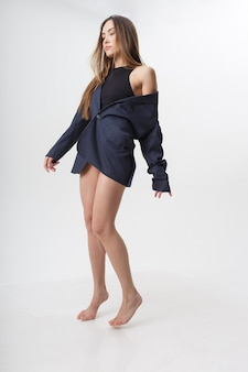 Porträt der jungen attraktiven asiatischen frau mit langen haaren, nackten füßen im schwarzen body, blauer anzug lokalisiert auf weißer wand. dünne hübsche frau, die auf cyclorama aufwirft. modellversuche der schönen dame