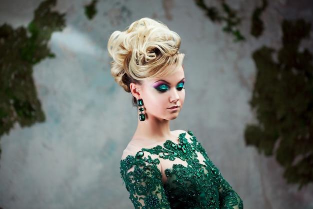 Porträt der jungen attraktiven blonden frau in einem schönen grünen kleid. strukturierter hintergrund, innenraum. luxusfrisur