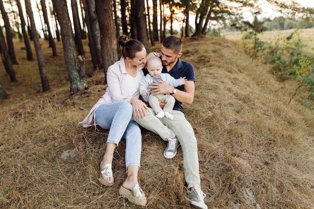 Porträt der jungen attraktiven familie mit dem kleinen kleinen sohn, der im schönen herbstkiefernwald am sonnigen tag aufwirft. hübscher mann und seine hübsche brünette frau