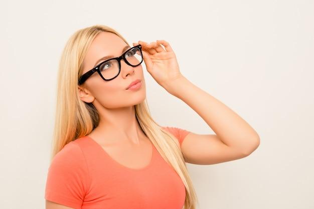 Porträt der jungen attraktiven frau, die ihre brille berührt und träumt