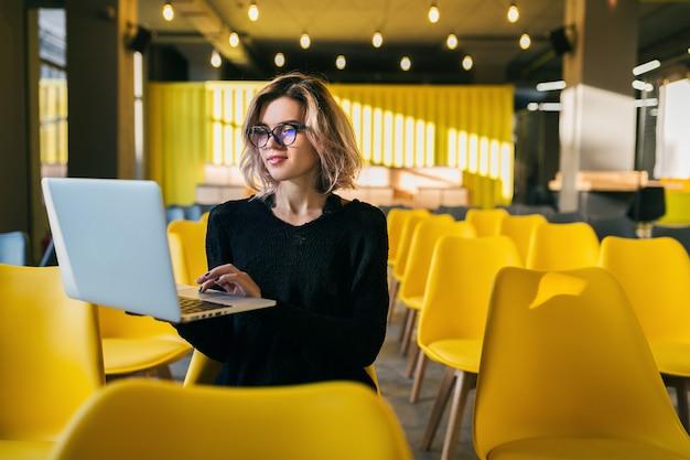 Porträt der jungen attraktiven frau, die im hörsaal sitzt, der auf laptop trägt, der brille trägt, student, der im klassenzimmer mit vielen gelben stühlen lernt
