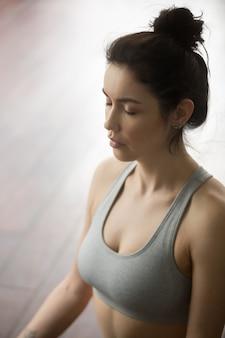 Porträt der jungen attraktiven frau, die in der yogahaltung meditiert