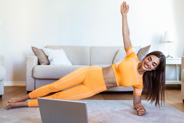Porträt der jungen attraktiven frau, die übungen macht, während online-lektionen auf ihrem laptop ansehen.