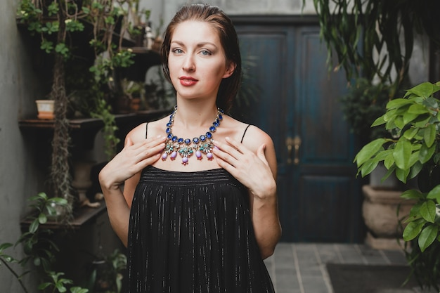 Porträt der jungen attraktiven frau im stilvollen schwarzen kleid, das an tropischer villa aufwirft, sexy, eleganter sommerstil, modische halskettenaccessoires, lächeln, schmuck, reine natürliche gesichtshaut