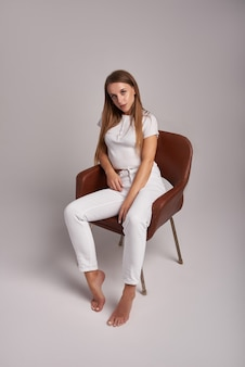 Porträt der jungen attraktiven frau mit den langen braunen haaren in den weißen jeans, lokalisiert auf weißem studiohintergrund. frau sitzt auf stuhl auf cyclorama.