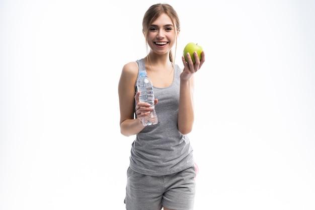 Porträt der jungen attraktiven frau mit grünem apfel und flasche