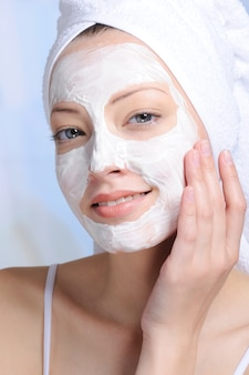 Porträt der jungen attraktiven frau mit kosmetischer maske auf ihrem gesicht