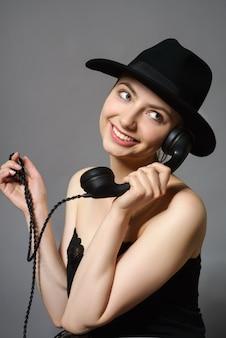 Porträt der jungen attraktiven frau mit weinlesetelefon