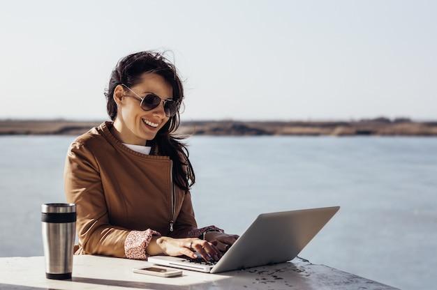 Porträt der jungen attraktiven geschäftsfrau, die draußen arbeitet