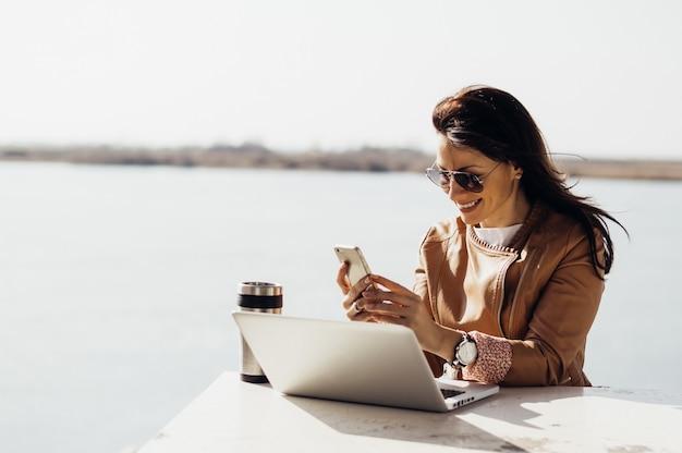 Porträt der jungen attraktiven geschäftsfrau, die draußen e-mails am telefon überprüft