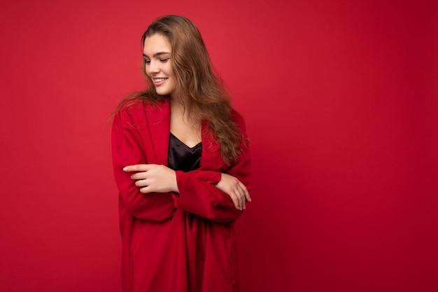 Porträt der jungen attraktiven kaukasischen hippie-frau in modischer freizeitkleidung. sexy sorglose weibliche person posiert isoliert in der nähe der roten wand im studio. positives modell mit natürlichem make-up. freiraum