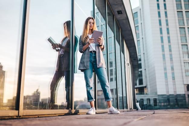 Porträt der jungen attraktiven lässig gekleideten geschäftsfrau mit einer tablette in den händen, die vor dem high-tech-glasgebäude des handelszentrums aufwirft