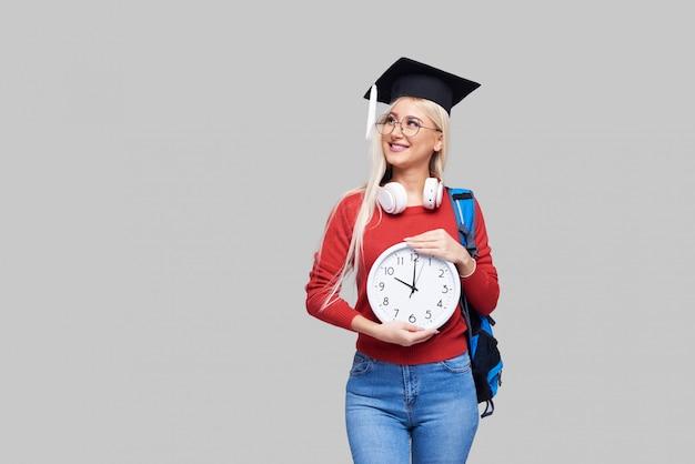 Porträt der jungen aufgeregten blonden studentin in der abschlusskappe mit rucksack, der großen wecker lokalisiert auf grauem raum hält. ausbildung im college. kopieren sie platz für text