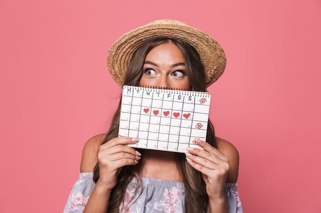 Porträt der jungen aufgeregten frau, die strohhut hält, die menstruationskalender hält