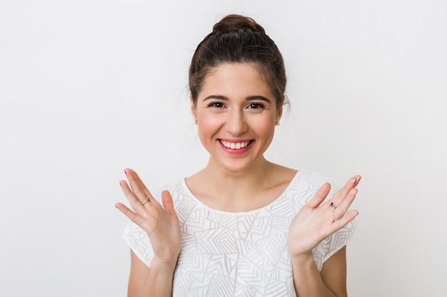 Porträt der jungen aufrichtigen lächelnden frau in der weißen bluse, positiver überraschter gesichtsausdruck, glücklich, händchen haltend, offene handflächen,