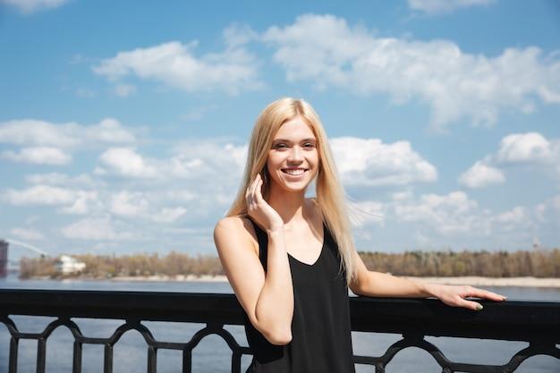 Porträt der jungen blonden frau, die nahe fluss steht