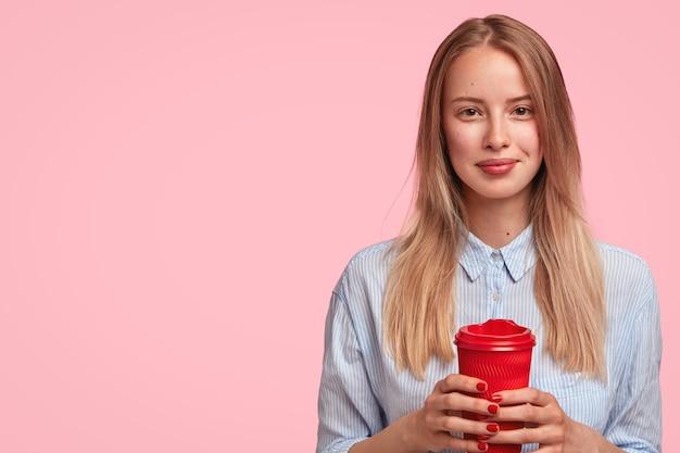 Porträt der jungen blonden frau, die tasse kaffee hält