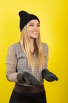 Porträt der jungen blonden frau in den schwarzen handschuhen und in der hutaufstellung und in der stellung.