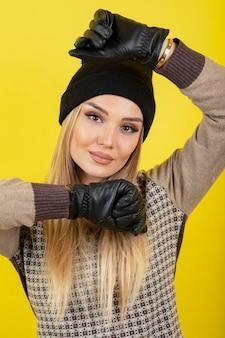 Porträt der jungen blonden frau in schwarzen handschuhen und hut