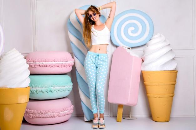 Porträt der jungen blonden frau mit langen haaren, die niedlichen trendigen pijama und sonnenbrille tragen, umgeben von großen süßigkeiten