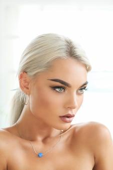 Porträt der jungen blonden frau mit mit gebräunter haut