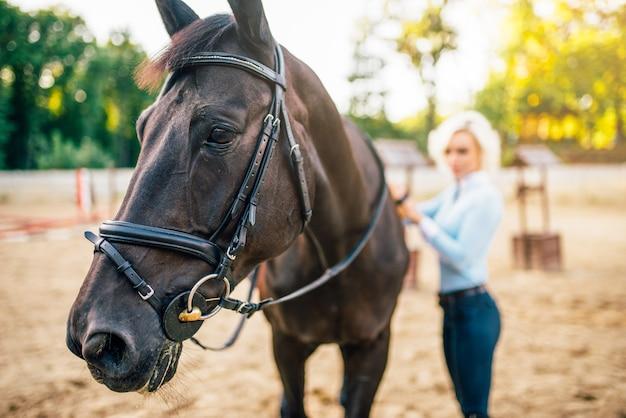 Porträt der jungen blonden frau mit pferd.