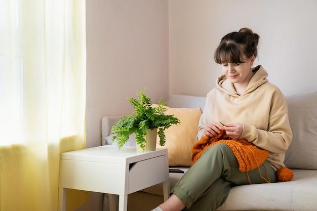 Porträt der jungen blonden kaukasischen frau, die allein auf sofa zu hause strickt. nahansicht.