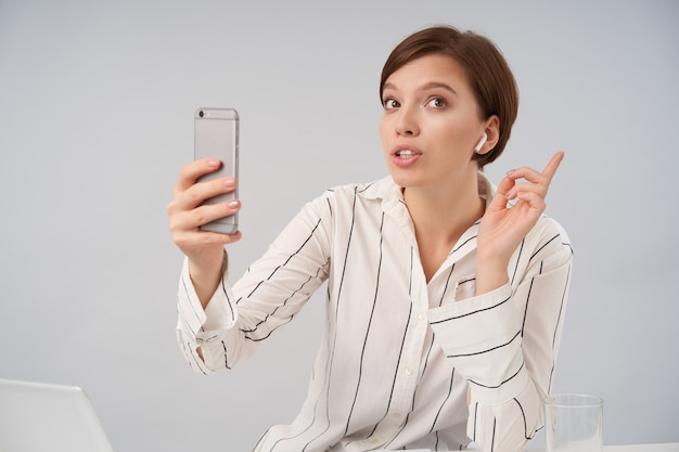 Porträt der jungen braunäugigen kurzhaarigen brünetten geschäftsfrau, die videoanruf mit ihrem smartphone macht, während auf weiß im gestreiften formellen hemd sitzt