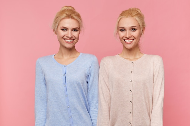 Porträt der jungen breit lächelnden glücklichen blonden zwillinge, die die kamera lokalisiert über rosa hintergrund betrachten.