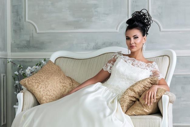 Porträt der jungen brünetten braut, die auf weinlesesofa im schönen hochzeitskleid sitzt