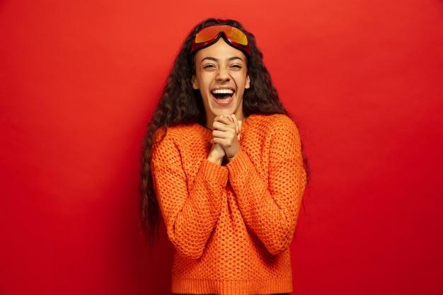 Porträt der jungen brünetten frau der afroamerikaner in der skimaske auf rot