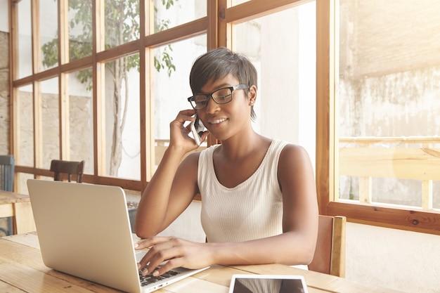 Porträt der jungen brünetten frau, die im café mit laptop sitzt