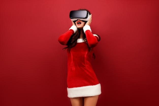 Porträt der jungen brunettefrau im roten samtkleid unter verwendung des virtuos