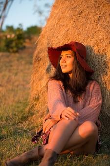 Porträt der jungen brunettefrau im weinberg mit stilvollem hut.