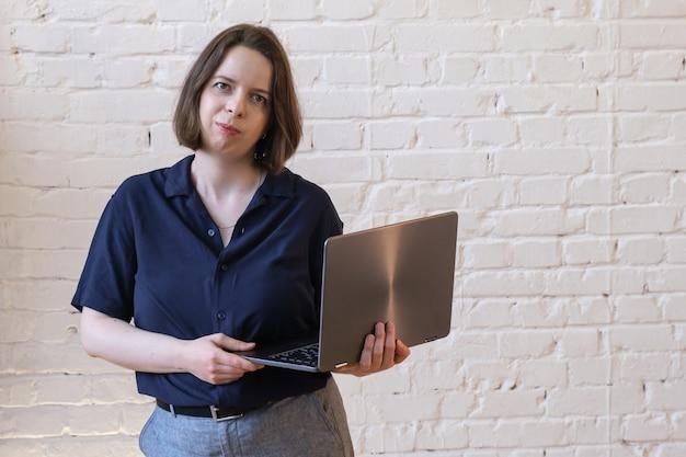Porträt der jungen brunettefrau mit dem schulterlangen haar auf weißem backsteinmauerhintergrund. frau im blauen hemd steht mit laptop in den händen und schaut in die kamera. platz für text rechts