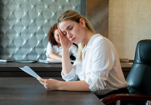 Porträt der jungen büroangestelltenfrau, die am schreibtisch mit dokumenten sitzt, die gelangweilt und überarbeitet arbeiten, die im büro sitzen