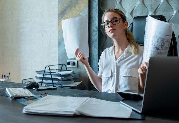Porträt der jungen büroangestelltenfrau, die am schreibtisch mit dokumenten sitzt, die kamera mit ernstem sicherem ausdruck auf gesicht betrachten, das im büro arbeitet