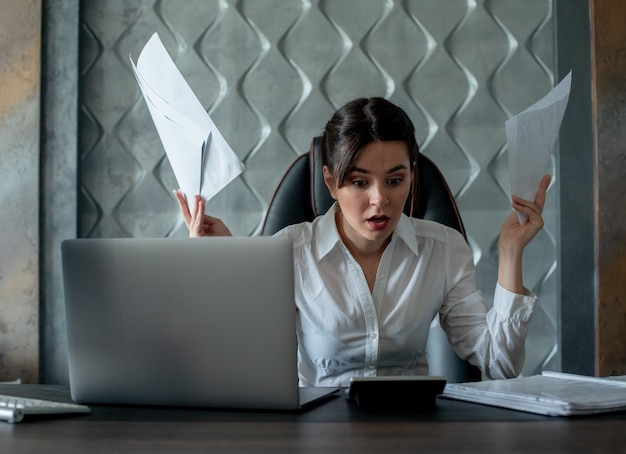 Porträt der jungen büroangestelltenfrau, die am schreibtisch mit dokumenten sitzt, die sie betrachten enttäuscht enttäuschte nervöse und gestresste arbeit im büro