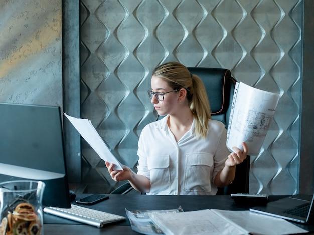 Porträt der jungen büroangestelltenfrau, die am schreibtisch mit dokumenten sitzt, die sie mit ernstem sicherem ausdruck auf gesicht betrachten, das im büro arbeitet
