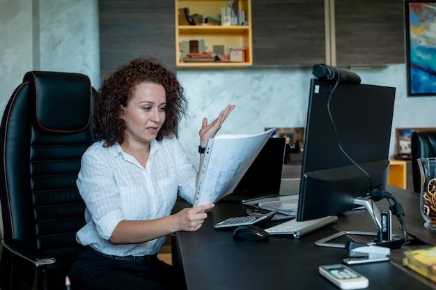 Porträt der jungen büroangestelltenfrau, die am schreibtisch mit dokumenten sitzt, die sie nervös und gestresst betrachten, die im büro arbeiten