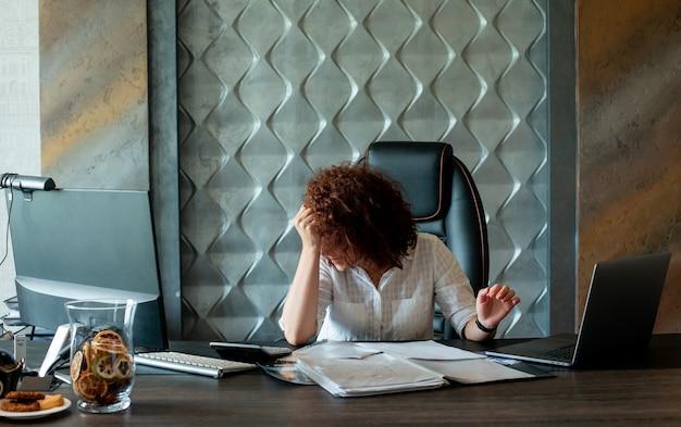 Porträt der jungen büroangestelltenfrau, die am schreibtisch mit dokumenten und laptop-computer sitzt, der im büro müde und überarbeitet schaut