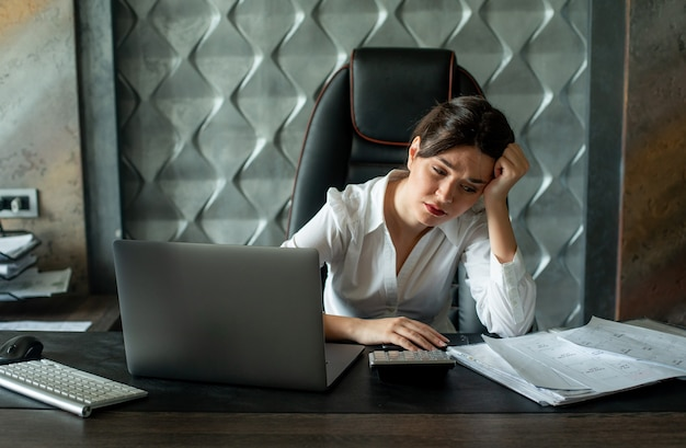 Porträt der jungen büroangestelltenfrau, die am schreibtisch mit dokumenten und laptop-computer sitzt, die müde und überarbeitetes arbeitsprozessbürokonzept suchen